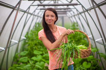 Young woman holding a basket of greenery and onion in the
