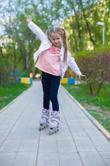 Little adorable girl on roller skates in the park