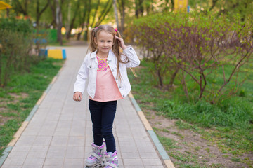 Adorable little girl on roller skates in the park