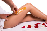 Sugaring: epilation with liquate sugar at legs. - 64841351