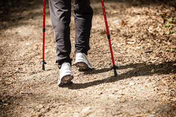 Nordic walking. Female legs hiking in forest or park.