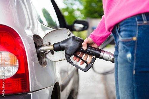 Lady pumping gasoline fuel in car at gas station. - 64842157