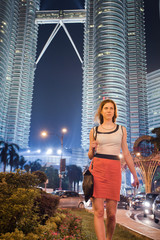 Girl goes on the background of two famous Petronas Twin Towers.