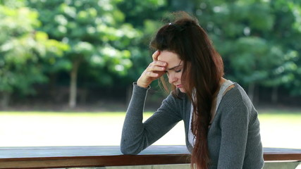A sad and depressed woman sitting outdoors