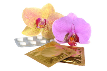 Film-coated tablets and condoms with two orchid flowers isolated