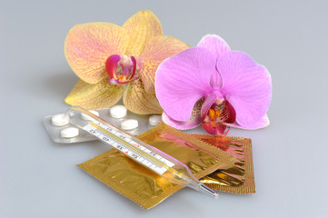 Film-coated tablets, condoms, thermometer with two orchid flower