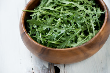 Wooden bowl with arugula lettuce, studio shot