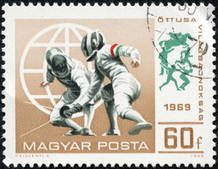 stamp printed in Hungary shows a fencing competitions