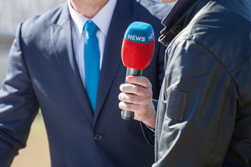 news journalist with microphone interviewing