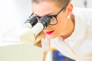 Kieferorthopädin arbeitet mit Mikroskop