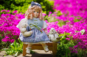 Collectable doll  in the blooming garden