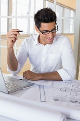 Casual architect working with laptop at desk