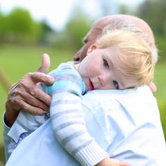 Grandfather comforting his little sad grandchild