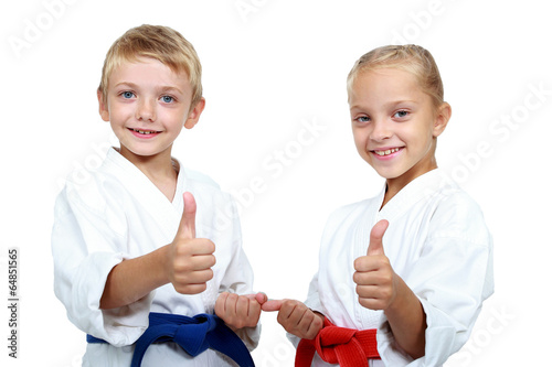 Fotobehang Vechtsporten Boy and girl in karategi are showing thumb super