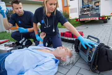Paramedics checking pulse of unconscious man