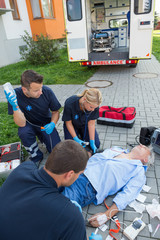 Paramedics treating injured man on street