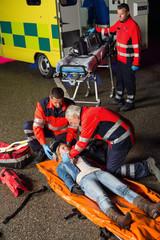 Emergency team helping injured motorcycle driver