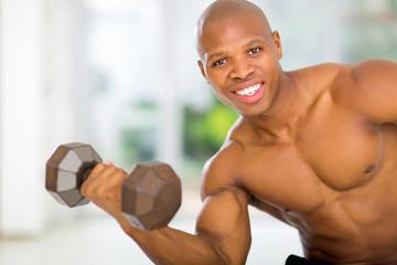 african man exercising with dumdbells at home
