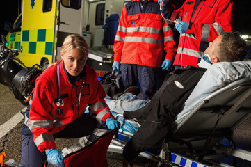 Paramedics assisting injured motorcycle man driver