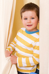little boy peeking out from behind the curtains.