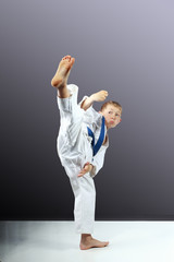 On a gray background little boy is beating mawashi geri