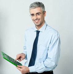 Corporate man using calculator
