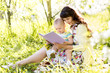 mom reading a book to baby outdoors