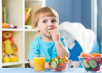 kid boy eating vegetables at home interior