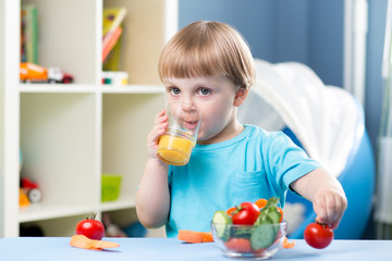 baby boy dinking juice at table in children room