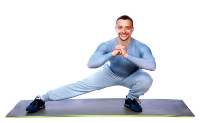 Happy sports man stretching on the mat over white background