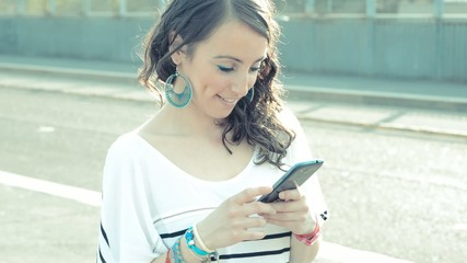 young beautiful hipster stylish woman using smart phone in the c