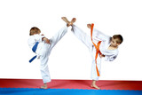 High kicks legs athletes are training on the red and blue mat