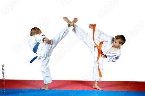Fotobehang Vechtsporten High kicks legs athletes are training on the red and blue mat