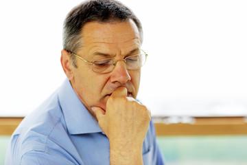 Senior man in glasses looking at camera