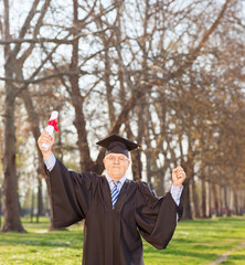 Mature man celebrating his graduation in park