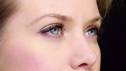 Pretty girl with eyeliner blinking close up