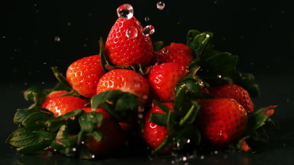 Water drops on strawberries on black surface