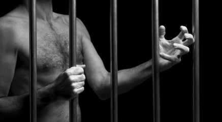 prisoner behind bars of a dark prison