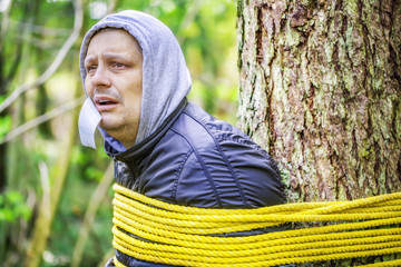 Man tied to a tree in the forest