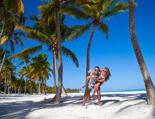Man giving piggyback ride to girlfriend at the Caribbean beach