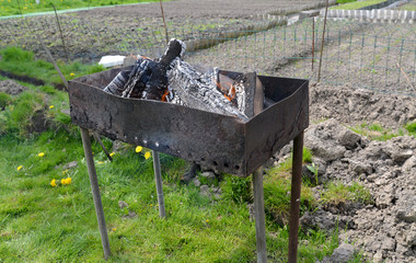 Brazier with burning firewood on a kitchen garden
