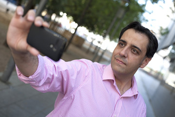 Caucasian man taking self portrait with mobile phone