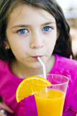Little girl drinking orange juice from straw