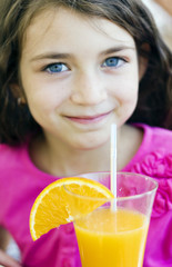 Adorable little girl drinking orange juice from straw