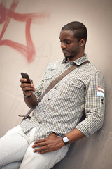 Young black man checking messages on his smart phone