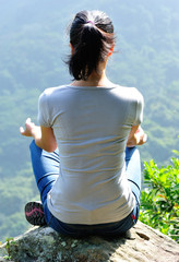 yoga woman meditation sit on mountain peak rock