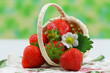 Strawberries in small wicker basket with copy space
