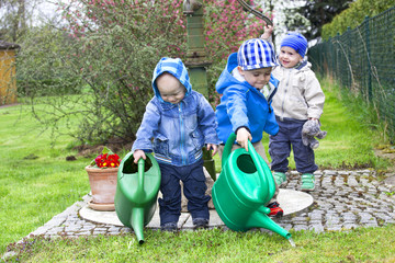 Children with watering can in the garden