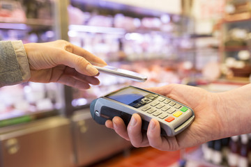 Woman paying with NFC technology on mobile phone, in supermarket