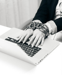 closeup photo of woman locked to laptop by chain